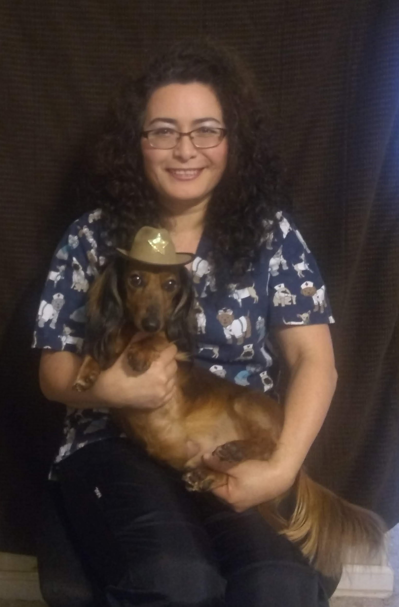 Team member Leticia holding a brown dachshund wearing a hat